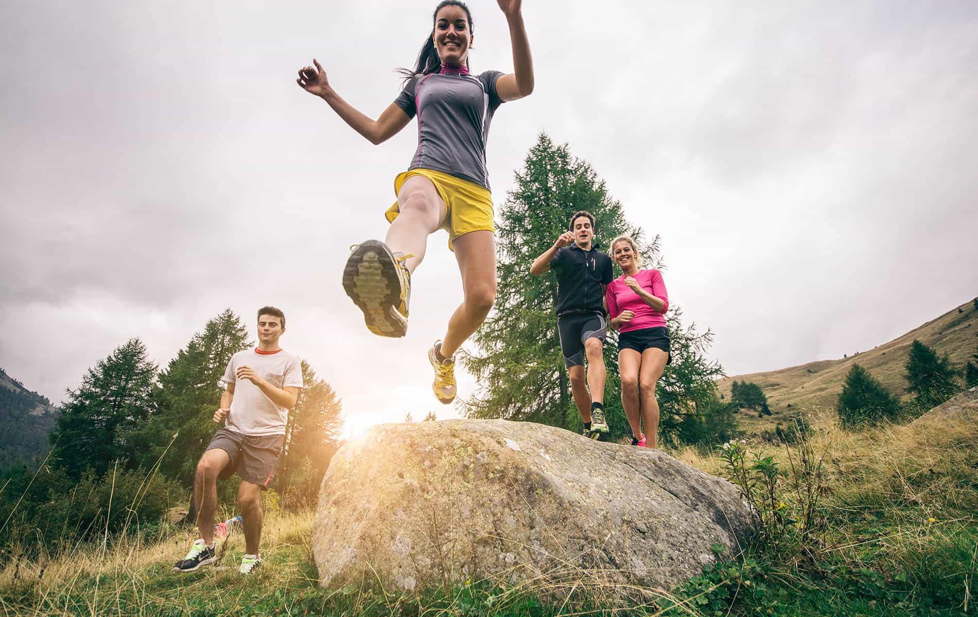 Vier Menschen joggen in den Bergen