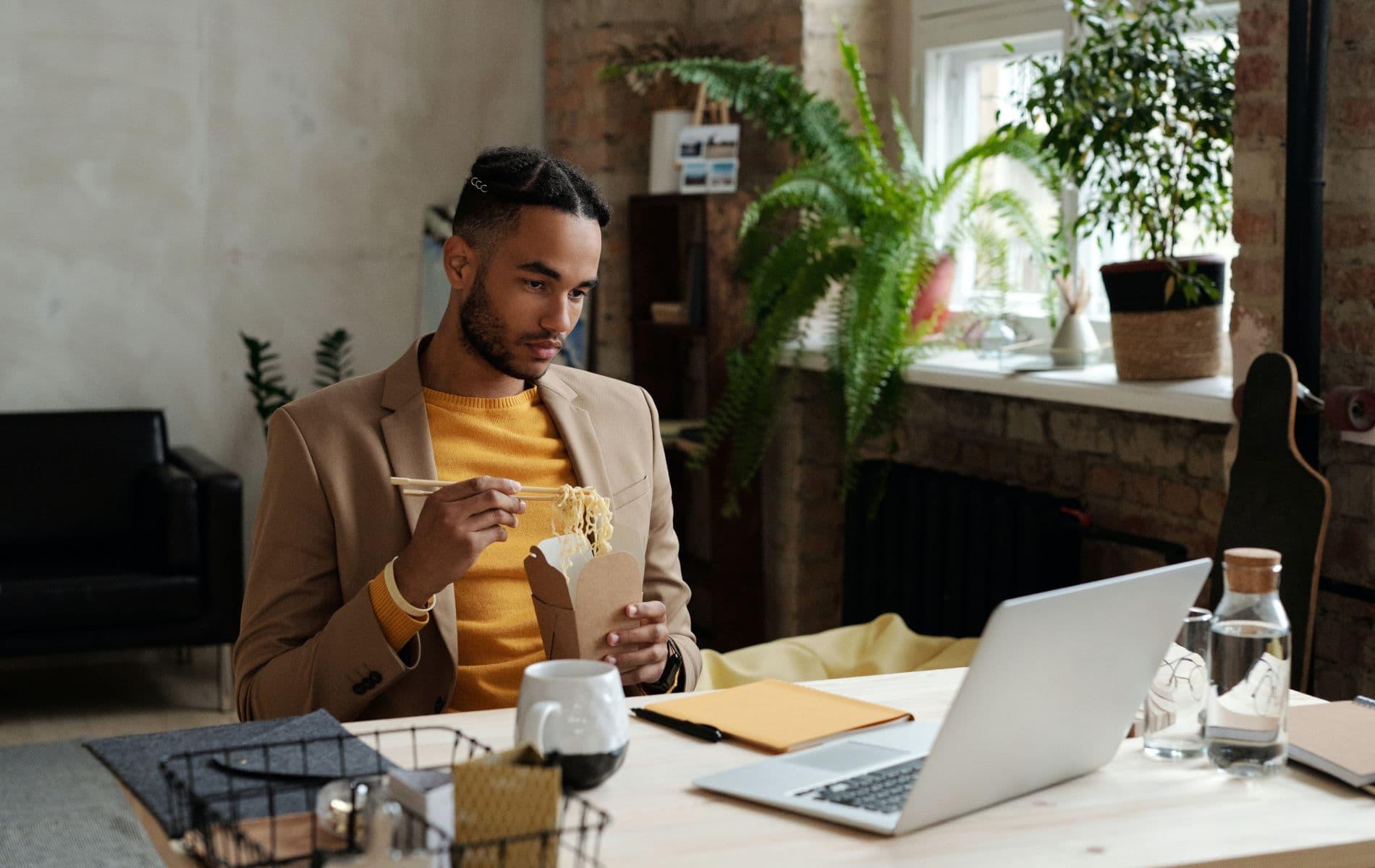 Mann isst im Home-Office seine Nudelbox