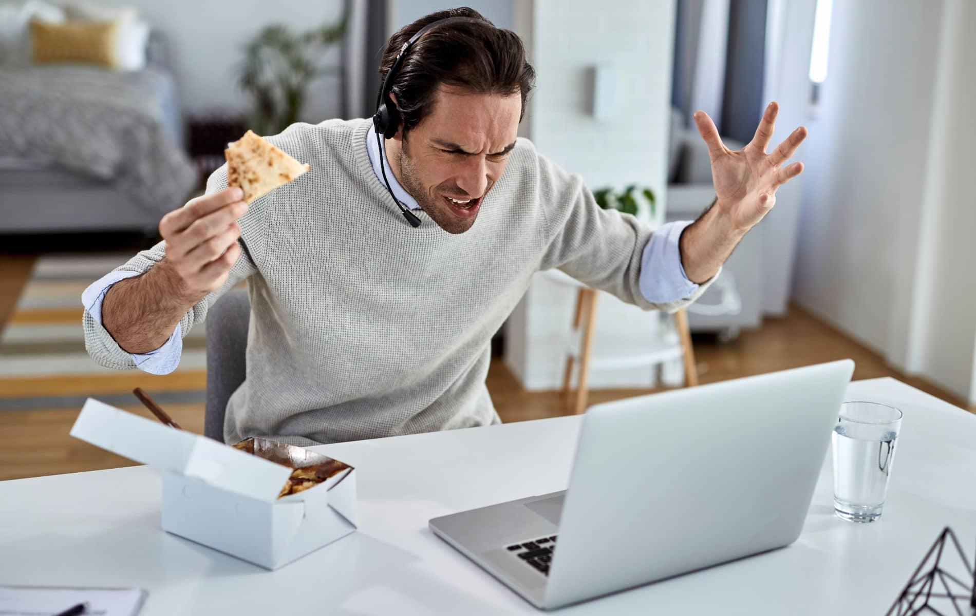 Mann isst im Home-Office gestresst seine Pizza