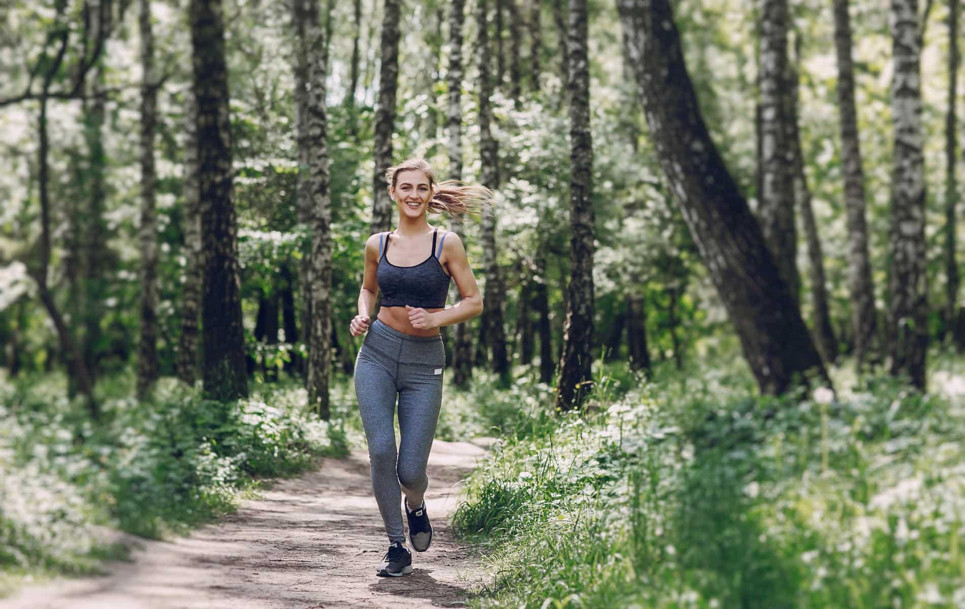 Frau joggt lächeln durch den Wald - Biohack Routine