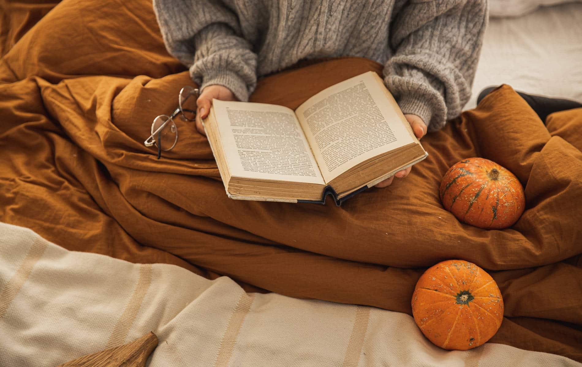 Frau liest im Bett entspannt ein Buch