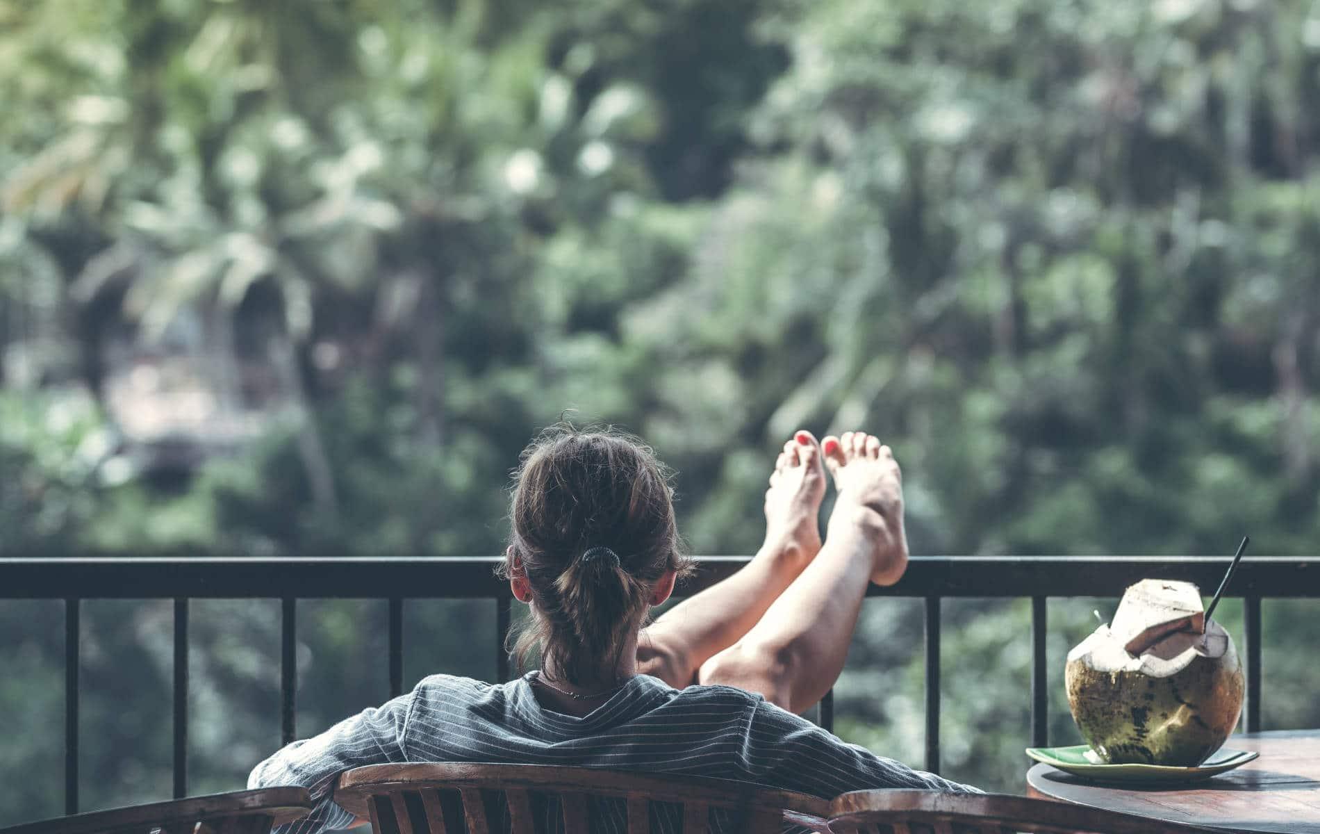Frau sitzt voll entspannt auf ihrem Balkon