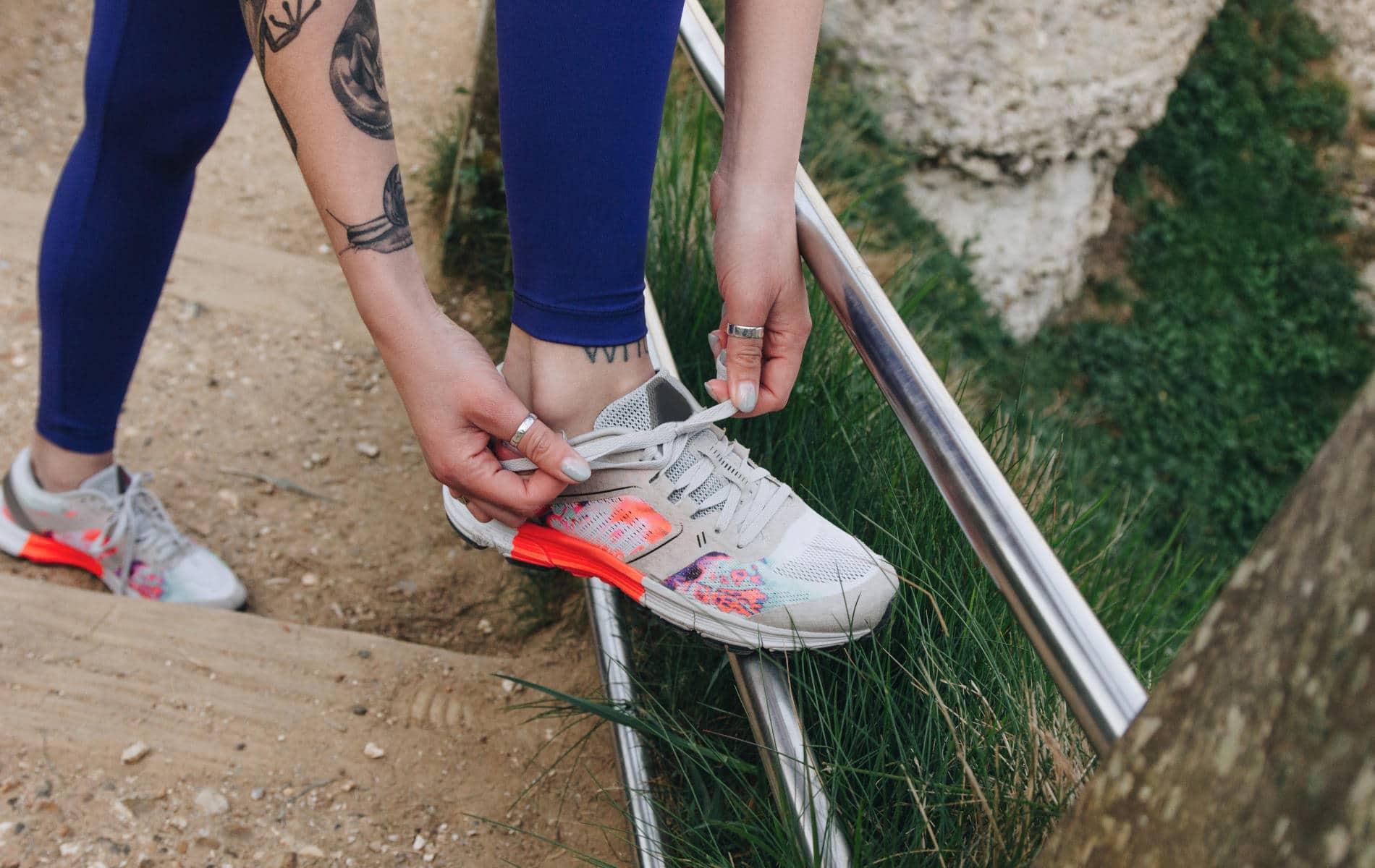 Frau zieht ihre Laufschuhe für einen Lauf an