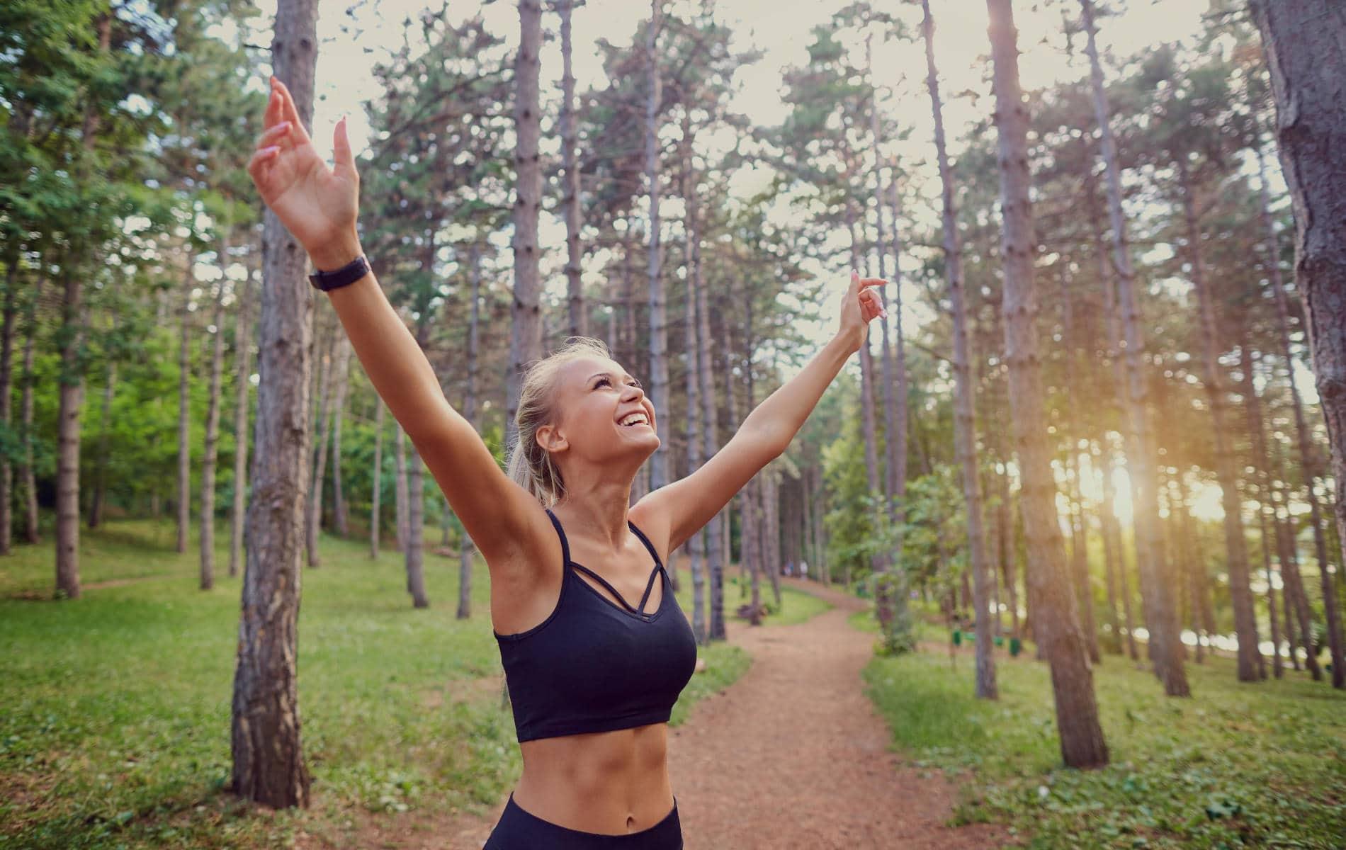 Mädchen feiert glücklich ihren Lauf im Wald