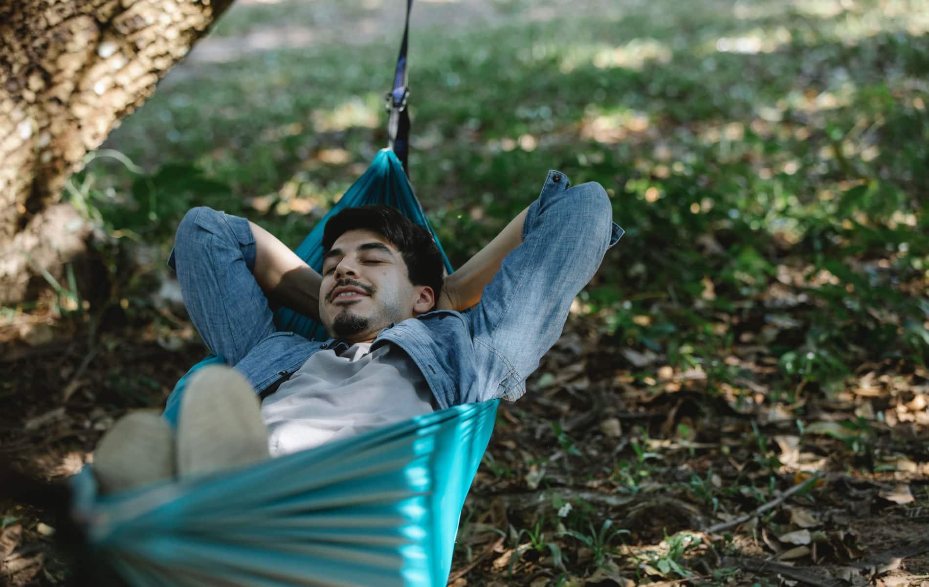 Mann liegt in der Hängematte und entspannt sich