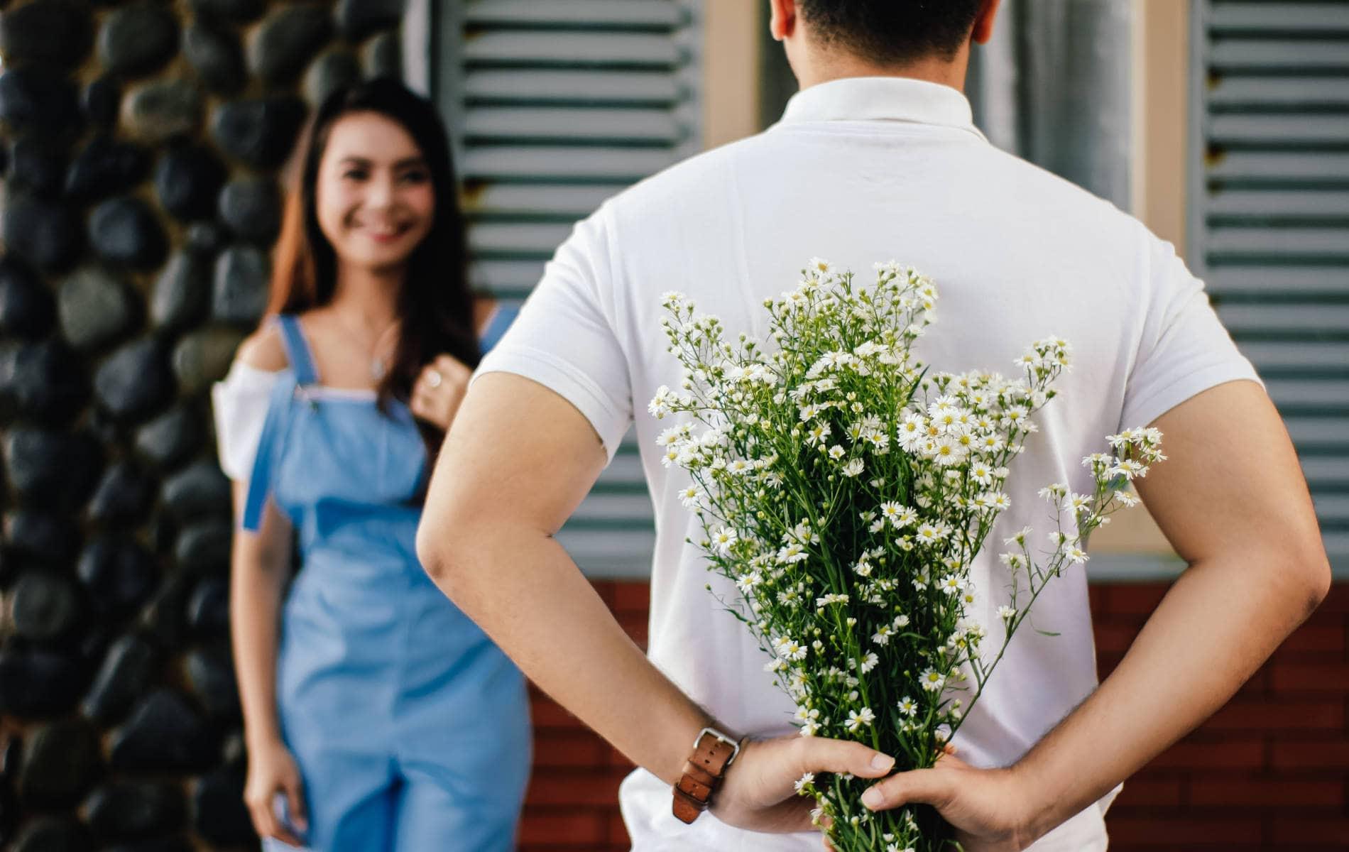 Mann schenkt seiner Freundin einen Blumenstrauß