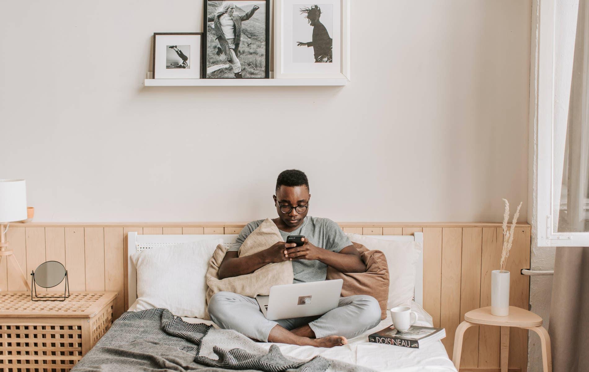 Mann sitzt im Bett vorm Handy im Home-Office