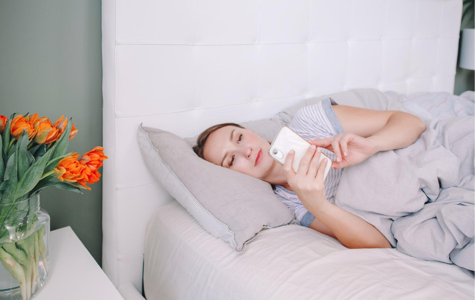 Junge Frau liegt mit Smartphone im Bett
