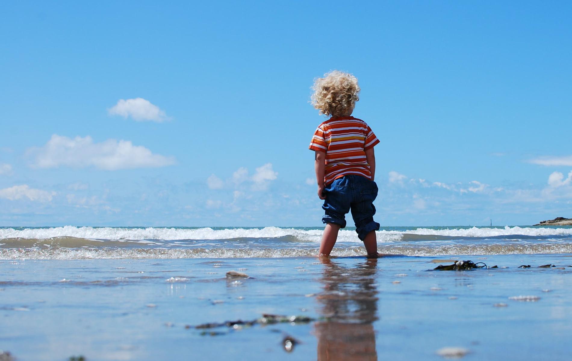 Kleines Kind steht im kalten Meer