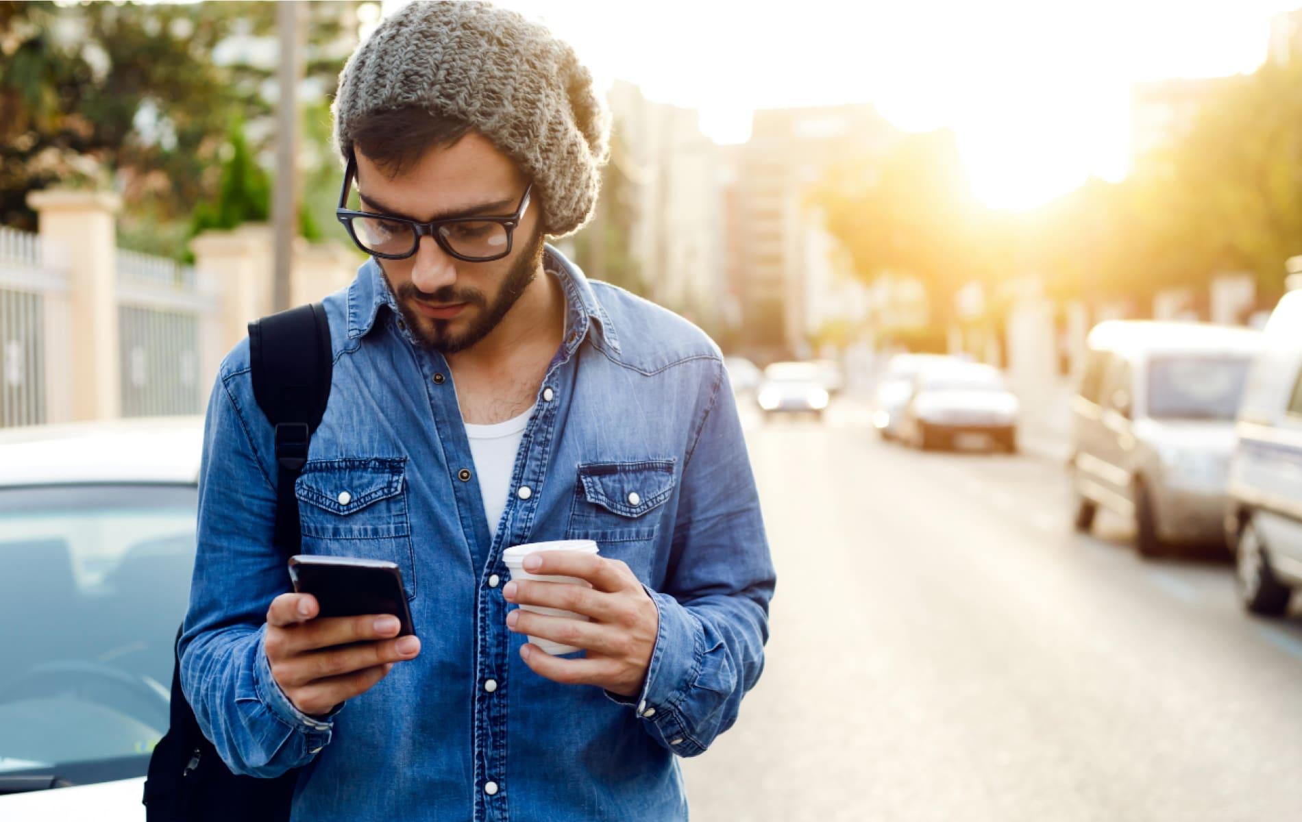 Junger Mann steht mit Smartphone am Straßenrand
