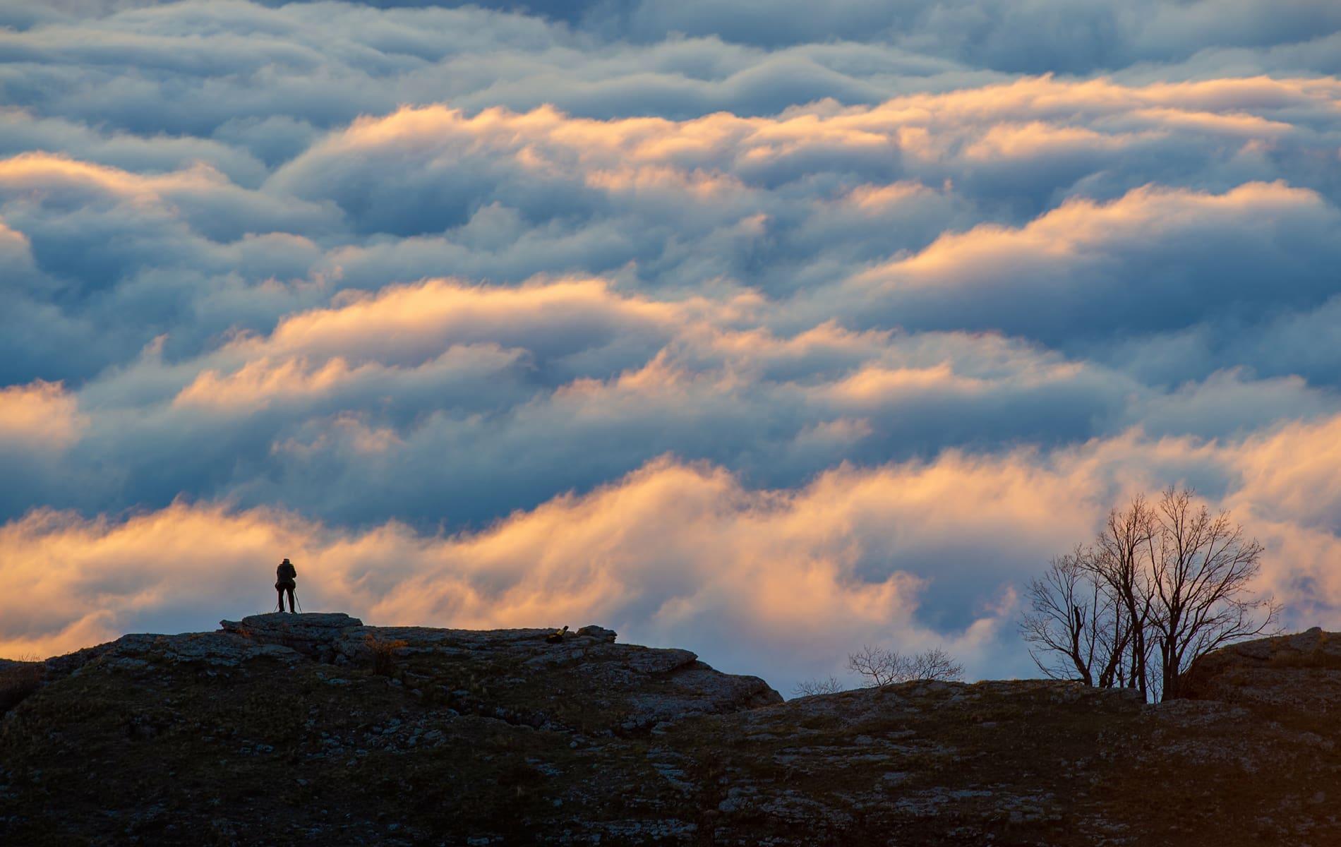 Mann steht auf hohem Berg und schaut auf Wolkenhimmel