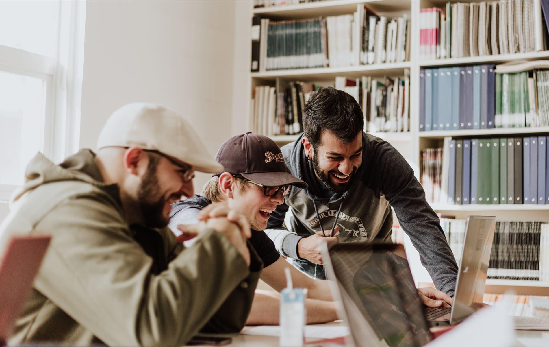 Drei Männer schauen lachend auf einen Laptop