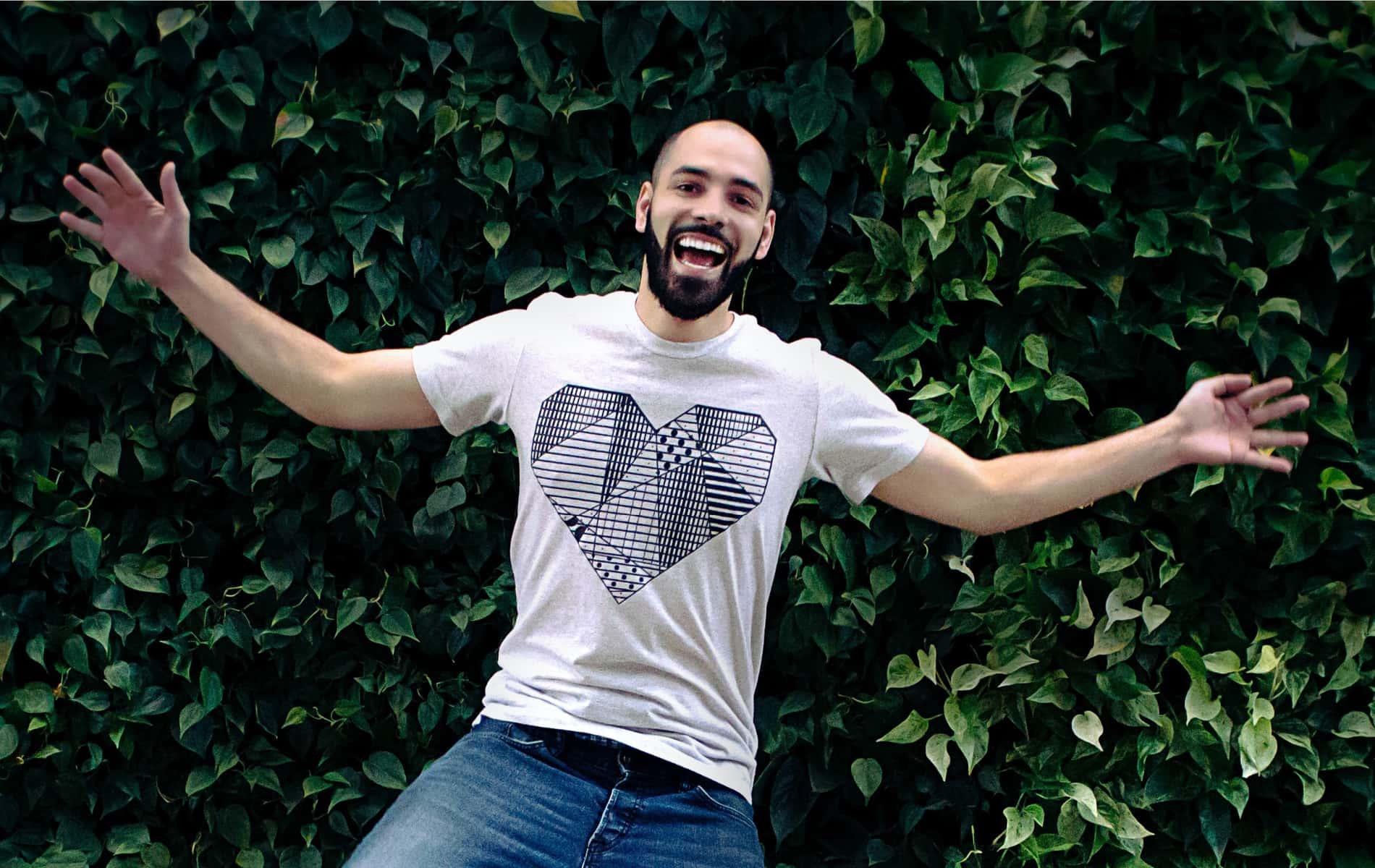 Mann liegt lachend auf grüner Hecke