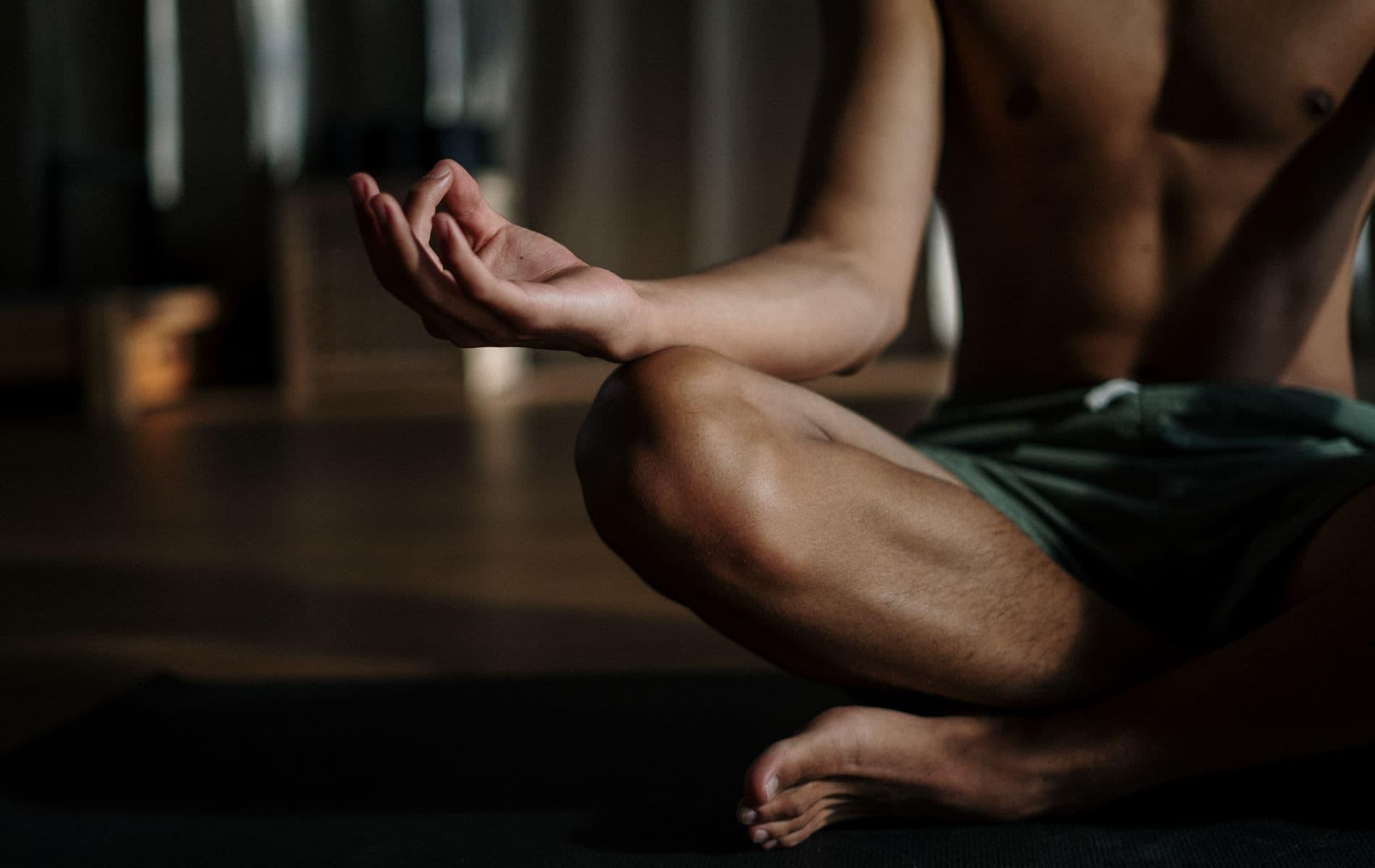 Mann sitzt meditierend auf dem Boden - Body-Mind-Power Biohacking