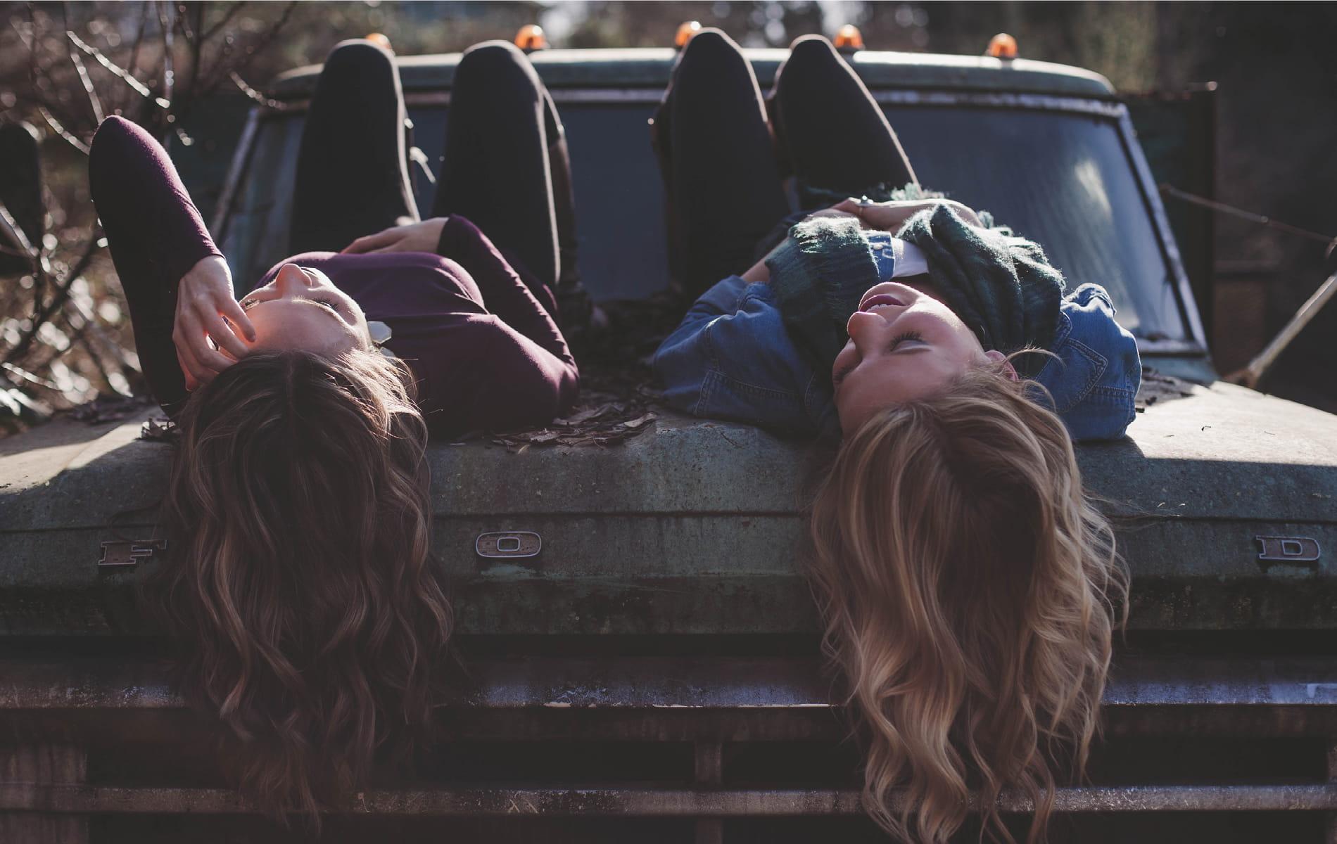 Zwei Frauen liegen mit dem Rücken auf einer Motorhaube
